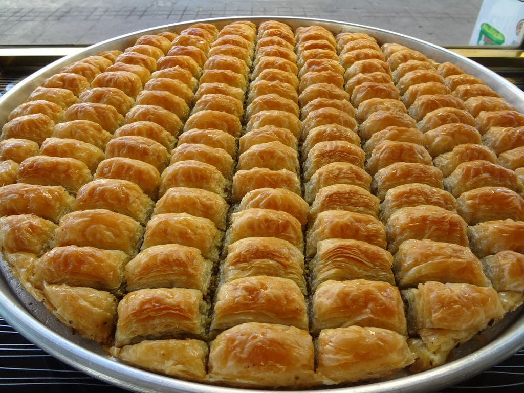Large round tray of fresh golden crispy walnut baklava, shiny from sugar syrup