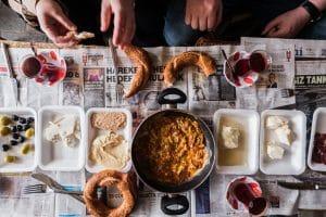 Taste of Two Continents food tour market breakfast of olives cheese eggs cream honey simit Turkish tea laid on newspaper